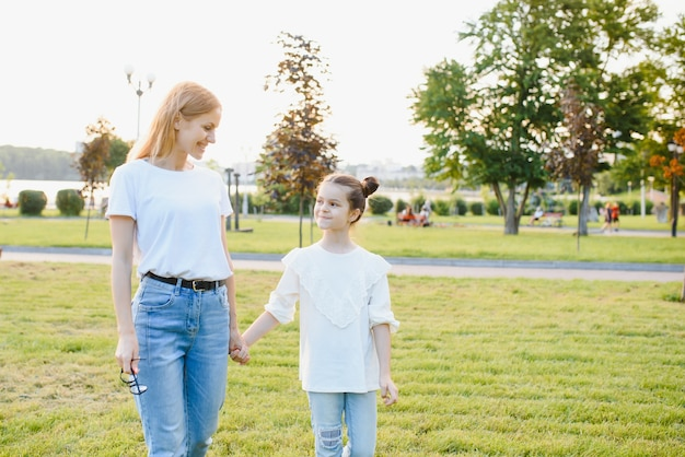 Portrait de mère avec fille dans un parc d'été. image avec mise au point sélective, effets de bruit et tonification. concentrez-vous sur la fille et la maman.
