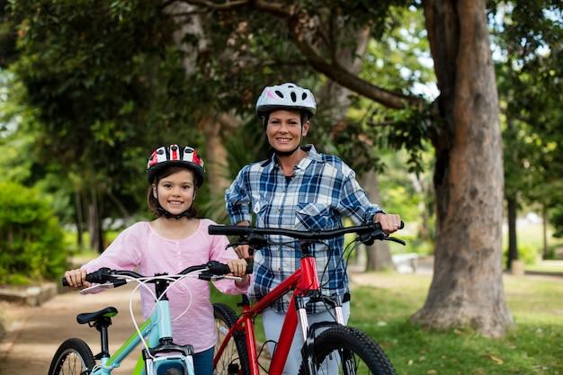 Portrait de mère et fille debout avec vélo dans le parc