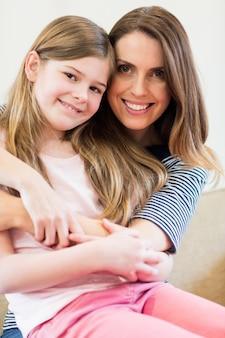 Portrait de la mère et la fille embrassant dans la salle de r