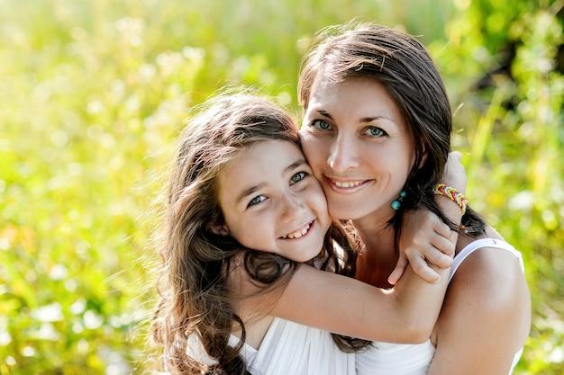 Portrait mère et fille étreignant. nature, temps ensoleillé