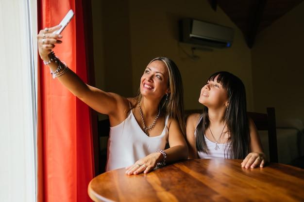 Portrait de mère et fille latina prenant un selfie