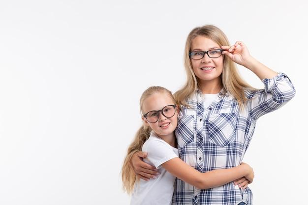 Portrait de mère et fille avec des lunettes sur un mur blanc