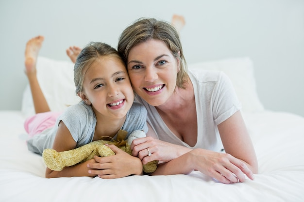 Portrait de mère et fille souriante allongée sur le lit dans la chambre