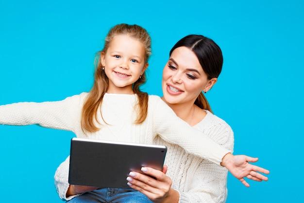 Portrait de mère et fille avec tablette assis sur le sol isolé sur le studio bleu.