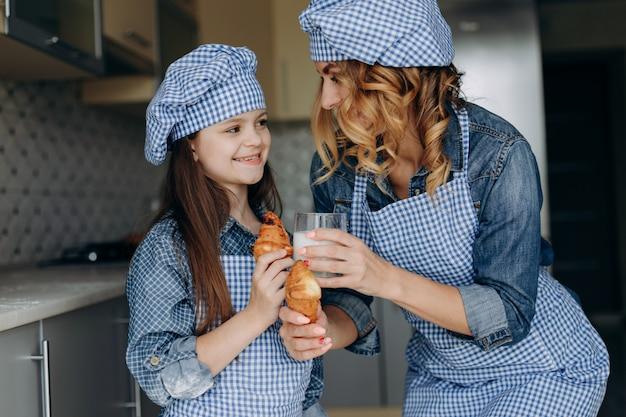 Portrait de mère et fille tenant des croissants et du lait. concept de famille