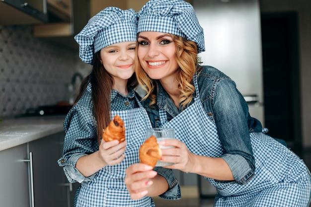 Portrait, de, mère fille, tenue, croissants, lait, et, regarder appareil-photo