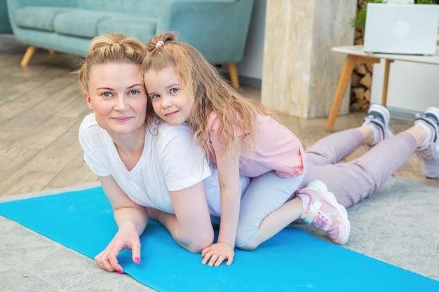 Portrait de mère et fille en tenue de sport allongée sur un tapis de yoga devant la fenêtre, s'embrassant