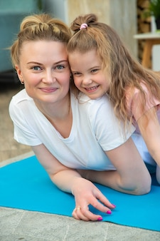 Portrait de mère et fille en tenue de sport allongée sur un tapis de yoga, étreignant et regardant la caméra.