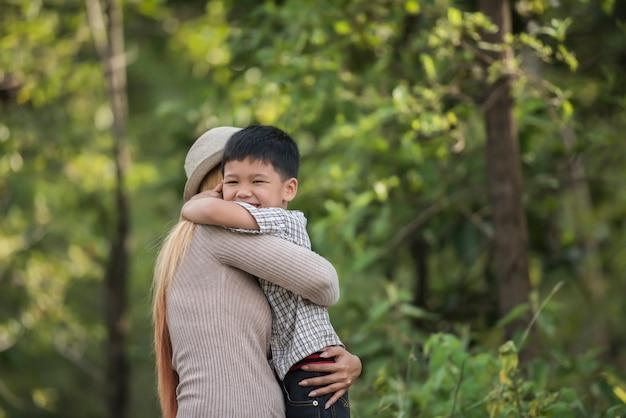 Portrait de mère et fils heureux câliner ensemble dans le parc. concept de famille