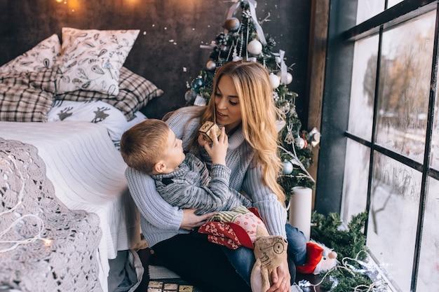 Portrait de mère heureuse et adorable bébé célèbrent noël. les vacances du nouvel an. tout-petit avec maman dans la salle décorée de façon festive avec arbre de noël et décorations.