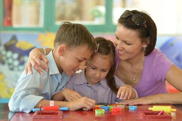 Portrait d'une mère heureuse jouant avec ses enfants