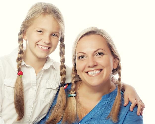 Portrait d'une mère joyeuse et sa fille souriant à l'avant