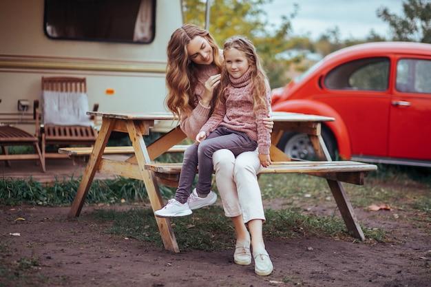 Portrait de mère et petite fille étreignant et relaxant dans la campagne en vacances camping car avec voiture rétro rouge