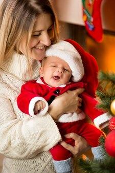 Portrait de mère posant avec bébé mignon santa