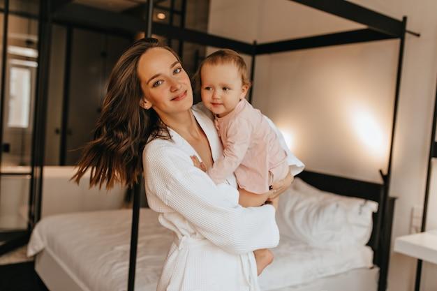 Portrait de mère positive et petite fille en tenue de maison posant dans la chambre. femme en peignoir étreignant bébé.