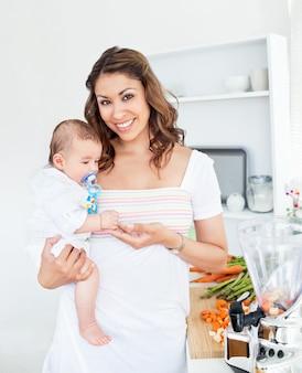 Portrait d'une mère radieuse tenant son bébé après avoir préparé le déjeuner