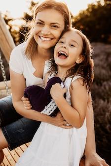 Portrait d'une mère et sa fille embrassant et assis sur une balançoire en bois regardant la caméra contre le coucher du soleil, souriant.