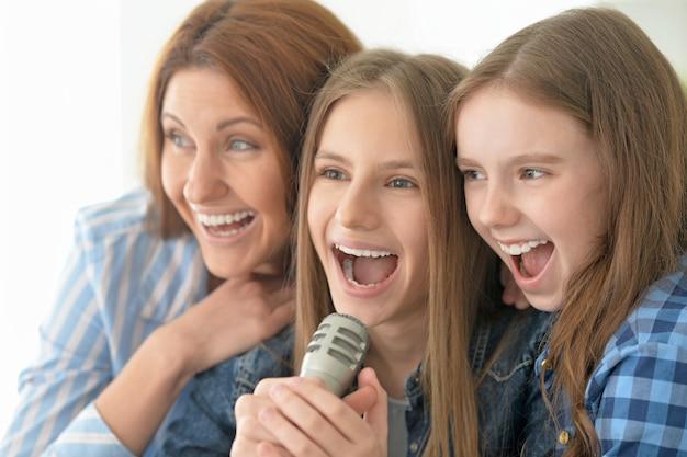 Portrait d'une mère et de ses filles heureuses chantant un karaoké