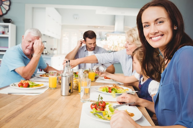 Portrait de mère souriante assise à la table à manger