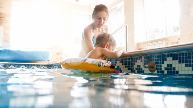 Portrait d'une mère souriante heureuse avec un petit fils de 3 ans nageant dans la piscine de la salle de sport. se détendre en famille, s'amuser et jouer dans l'eau