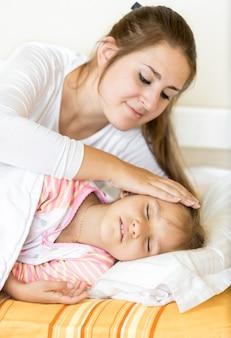 Portrait de mère tenant la main sur sa fille endormie avec soin