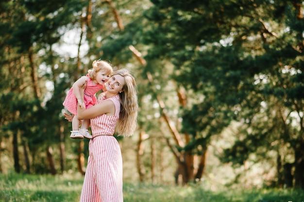 Portrait d'une mère tient sa fille sur les mains sur la nature pendant les vacances d'été. maman et fille jouant dans le parc à l'heure du coucher du soleil. concept de famille sympathique. fermer.