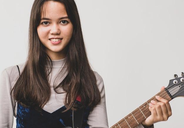Portrait d'un mignon adolescent thaï-turc souriant tenant et jouant de la guitare électrique. guitariste métis junior jouant de l'instrument tout en regardant la caméra isolée sur fond blanc