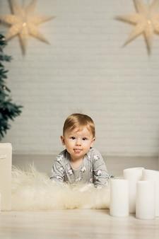 Portrait d'un mignon bambin jouant sur le sol près d'un arbre de noël. joyeux noël et joyeuses fêtes.
