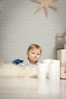 Portrait d'un mignon bambin jouant sur le sol près d'une décoration de noël.