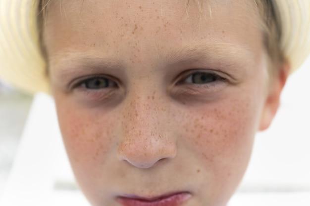 Portrait de mignon beau garçon au chapeau avec des taches de rousseur en gros plan un garçon avec un regard sérieux et triste et