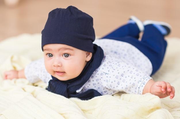 Un portrait d'un mignon bébé nouveau-né dans un blanc comme un chapeau ourson couché sur le ventre