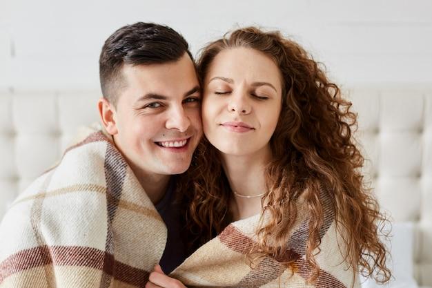 Portrait de mignon couple heureux assis dans son lit s'embrassent. belle femme aux longs cheveux bouclés est assise les yeux fermés avec son mari