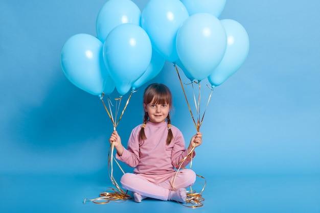 Portrait de mignon enfant d'âge préscolaire posant contre le mur bleu avec des ballons