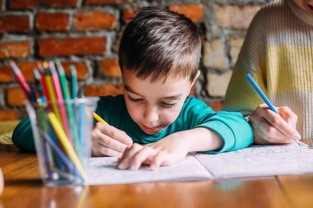 Portrait d'un mignon garçon d'âge préscolaire heureux à la maison ou dans un café