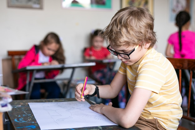 Portrait de mignon garçon avec un stylo et du papier au bureau en classe