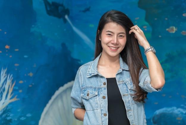 Portrait de mignon jeune étudiant en jeans veste sourire sur fond de l'eau