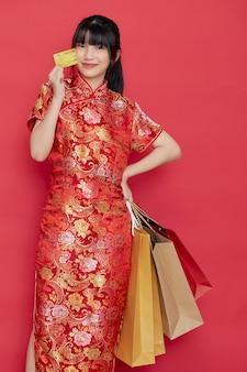 Portrait mignon jeune femme asiatique porter une robe chinoise avec un sac à provisions et une carte de crédit pour le nouvel an chinois sur un mur rouge