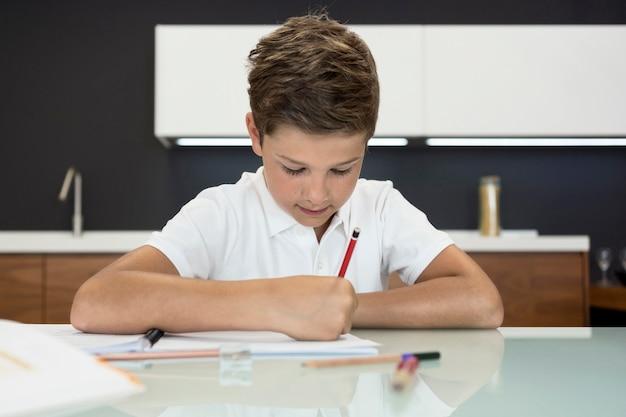 Portrait de mignon jeune garçon à faire ses devoirs