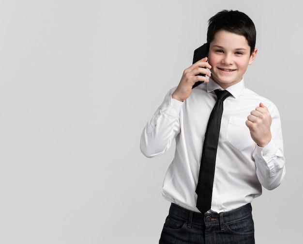 Portrait de mignon jeune garçon parlant sur téléphone mobile