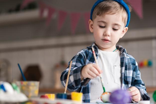 Portrait de mignon jeune garçon peignant des oeufs pour pâques