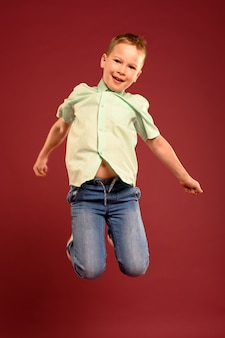 Portrait de mignon jeune garçon sautant