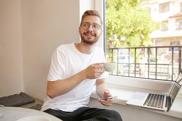 Portrait de mignon jeune homme avec barbe et lunettes, travaillant à distance avec un ordinateur portable, tenant un smartphone et un café dans ses mains, étant positif et heureux