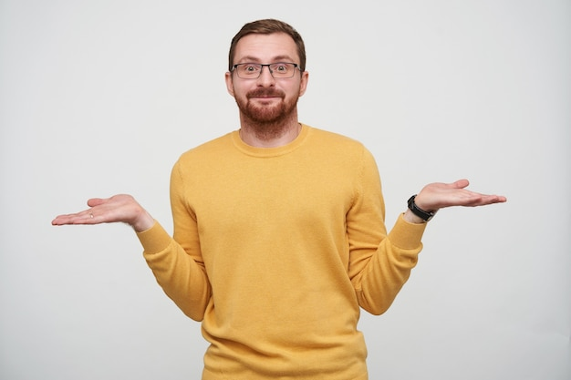 Portrait de mignon jeune homme barbu en lunettes avec des cheveux courts bruns haussant les épaules avec les bras ouverts et en gardant les lèvres pliées en position debout