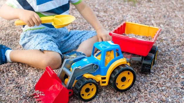 Portrait d'un mignon petit garçon de 3 ans assis sur l'aire de jeux du parc et jouant avec un camion jouet en plastique coloré. enfant s'amusant et jouant dehors avec des jouets