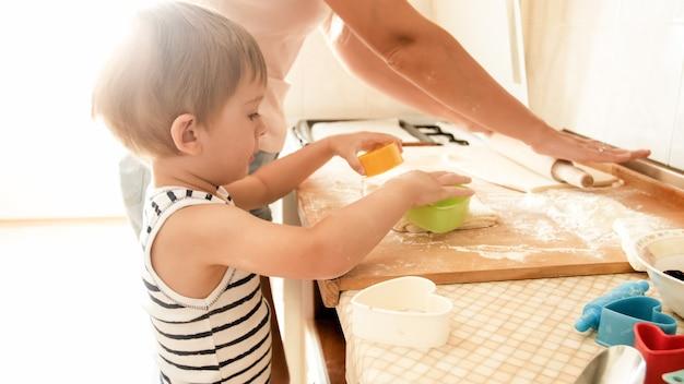 Portrait D'un Mignon Petit Garçon De 3 Ans Cuisinant Des Biscuits Avec Sa Mère. Cuisine Familiale Et Pâtisserie Photo Premium