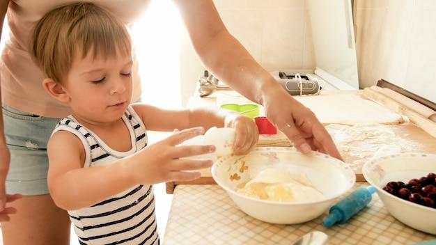 Portrait d'un mignon petit garçon de 3 ans cuisinant des biscuits avec sa mère