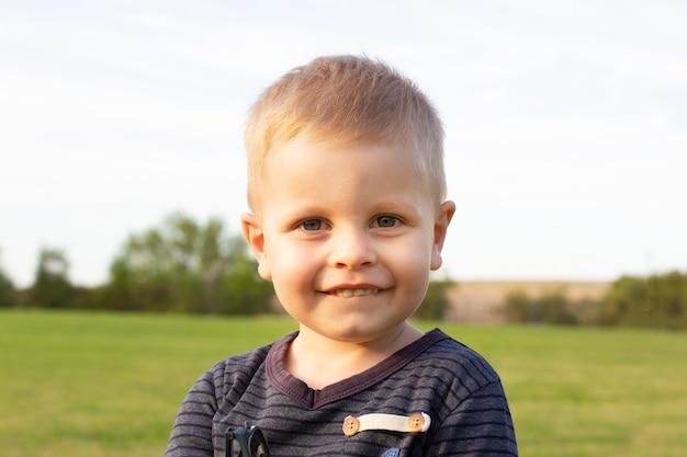 Portrait de mignon petit garçon de 3 ans en plein air