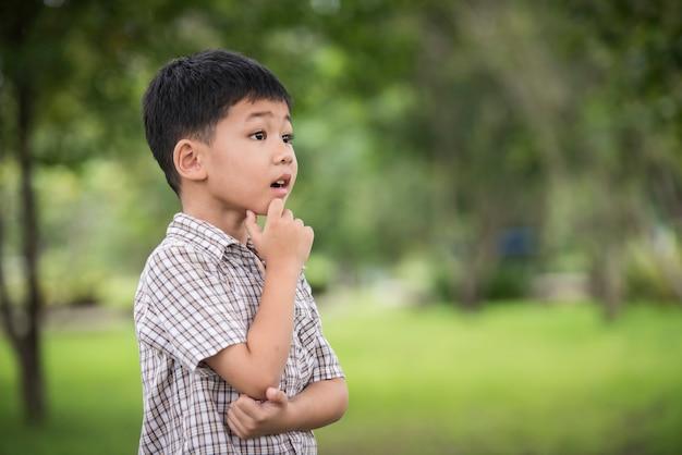 Portrait de mignon petit garçon asiatique à la main sous le menton et penser en se tenant debout