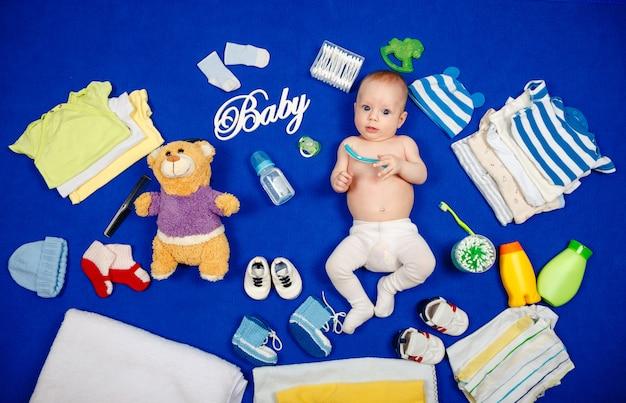 Portrait mignon petit garçon aux yeux bleus allongé sur le lit