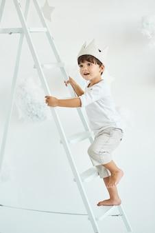 Portrait d'un mignon petit garçon en couronne sur une échelle blanche parmi les nuages sur un blanc